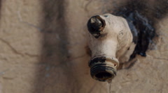 Close up of old grunge faucet leaking water on graffiti wall Stock Footage