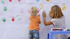 Child painting color handprints on the wall with mother and giving five Stock Footage