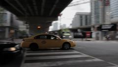 Pan with yellow taxi cab under bridge to cityscape Stock Footage