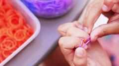 Little girl making finger bracelets Stock Footage