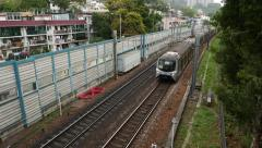 MTR train quickly moves from afar, overground part of the line Stock Footage