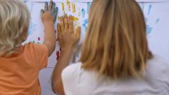 Cute child making handprints with color paint with mother. Stock Footage