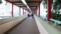 Ordinary people walking at footbridge, camera move through pedestrian passage Stock Footage