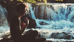 Catholic young man making the sign of the cross and praying near a river Stock Footage