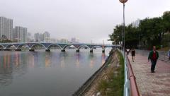 Runner lane at river front, twilight, people walking, beautiful bridge ahead Stock Footage