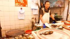 Cheerful seafood seller in market, close up view around fish shop stall Stock Footage