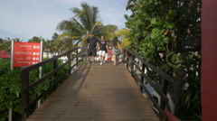 Girl with long hair walking and running on the bridge at Grand Oasis Cancun Stock Footage