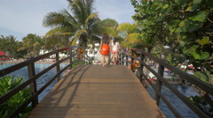 Girl in an orange skirt crossing the bridge at Grand Oasis Cancun Stock Footage