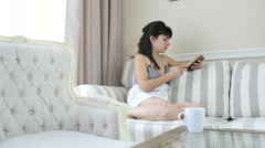 Woman in a nightdress is reading a book at home, a cup of coffee on the table Stock Footage