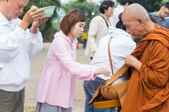 People put food offerings in a Buddhist monk's alms bowl to make great merit Stock Photos