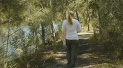 Woman walking in the woods - 90 degree shutter 25p Stock Footage