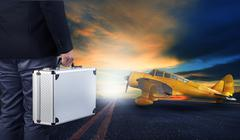 Business man with metal strong luggage standing in airport runways with yello Stock Photos