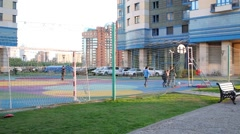 Children play football and basketball on court next to building Stock Footage