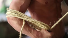 Arm of young muscular half-naked man winding rope on his hand Stock Footage