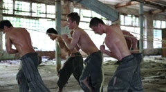 Five half-naked guys pull ropes in abandoned building Stock Footage