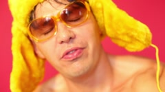 Face of handsome man in fur cap and glasses in red studio Stock Footage