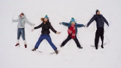 Stock Video Footage of Four people family lay on snow and wave hands at winter day