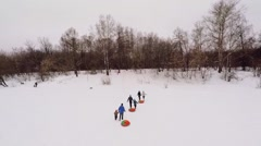 Six people run by snow slope with inflatable inner tubes Stock Footage