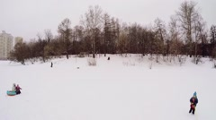 People ride on inner tubes at winter day. Aerial view Stock Footage