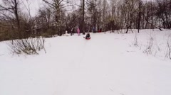 Woman with girl slide by snow slope on inner tube at winter Stock Footage