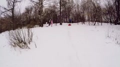 Kid lay on inner tube and ride by snow slope at winter day. Stock Footage