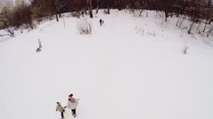 People ride on inner tubes by snow slope at winter day Stock Footage