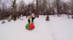 Woman with little boy ride on inner tube by snow slope Stock Footage