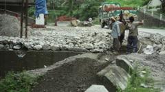Himalaya mountain road workers loading heavy load, long shot Stock Footage