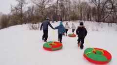 Parents with kids run by snow slope with inner tubes Stock Footage