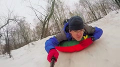 Man lies on top of an inner tube and slides by snow slope Stock Footage