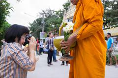 People put food offerings in a Buddhist monk's alms bowl for good merit Stock Photos