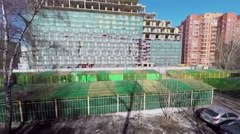 Car rides by street near construction site of apart-complex RE:Form Stock Footage