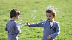 Adorable little boys, playing together with soap bubbles in the park Stock Footage