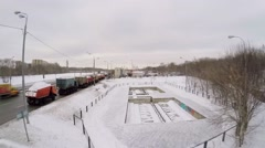 Several trucks with snow stand near snow-smeltery during snowfall Stock Footage