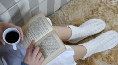 Woman in a nightdress and warm slippers is reading a book at home Stock Footage