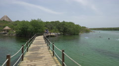Crossing the wooden bridge at Xel-Ha Park in Cancun Stock Footage