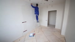 Worker standing on a ladder and puts fiberglass to the wall Stock Footage