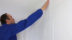 A man in work clothes glues to the wall sheet of the fiberglass - stock footage