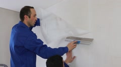 Two workers smooth fiberglass sheet on the wall with a spatula Stock Footage