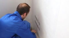 Worker cuts off excess of fiberglass in the corner of the room - stock footage
