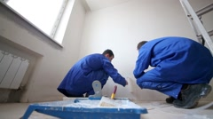 Two workers glues fiberglass sheet to wall, smoothing it by roller Stock Footage