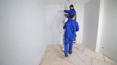 Worker glues fiberglass sheet to the wall above the doorway Stock Footage