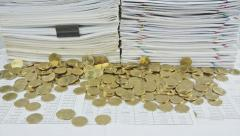 Stack paper and gold coins on table time lapse Stock Footage