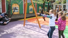 Girls rocking swing with the boys in the park Hermitage. Stock Footage