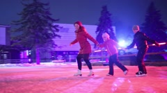 Family of three skates at rink with colored light holding hands Stock Footage