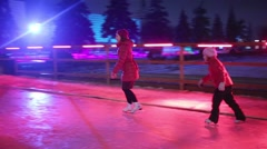 Mother and daughter skates at rink with colored light Stock Footage