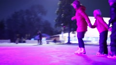 Mother and two children skates at rink holding hands Stock Footage
