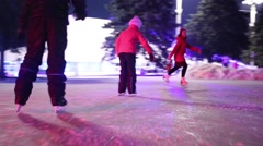 Family of three skates at ice rink with colored light Stock Footage