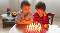 Adorable cute boys, blowing candles on a birthday cake at home Arkistovideo