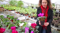 Beautiful woman holding pot with flower in the greenhouse Stock Footage